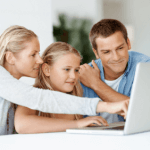 girl on computer with parents